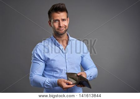 A poor handsome young man feeling stressed looking in to the camera and showing his empty wallet.