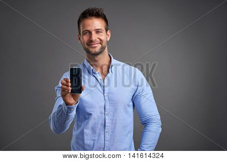 A confident handsome young man showing his phone to the camera