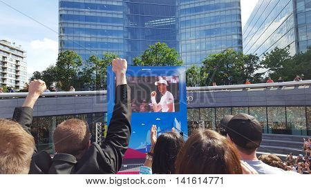 London, England - July 10, 2016 Crowd watching Wimbledon men's final tennis match on big screen at London Bridge City Summer Festival