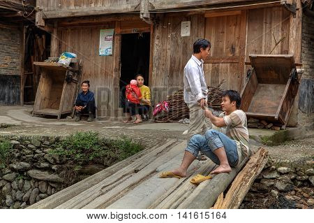 Zhaoxing Dong Village Guizhou Province China - April 9 2010: Rural residents in China Dong peoples resting on the village street near the wooden farmhouses.