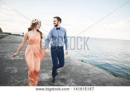 Beautiful loving couple, pride with long dress walking on pier.