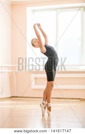 Young dancer doing an exercise at ballet class