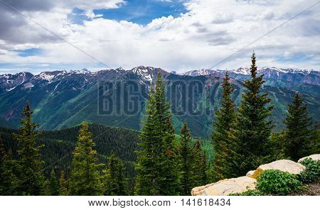 Aspen Highlands Overlook View in the Rocky Mountains near Aspen Colorado tall Pine Trees , deep valley and summer time sunshine with lush green Alpine Forests and Aspen Trees Summer Landscape
