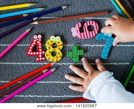 Colorful crayons and figure with small toddler hands. Preschool and kindergarten background. Back to school concept.