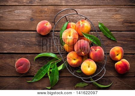 fresh peaches fruits with leaves in basket on wooden table