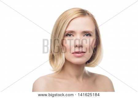 Beautiful middle aged woman with smooth skin and short blond hair. Beauty shot. Isolated over white background. Copy space.