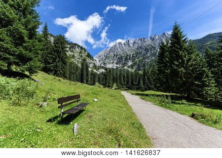 Idyllic mountain scene with a bench in the foreground. Austrian alps Tyrol Wilder Kaiser