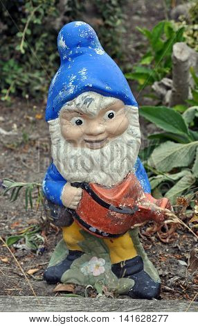 Cute old weathered ceramic garden gnome decoration