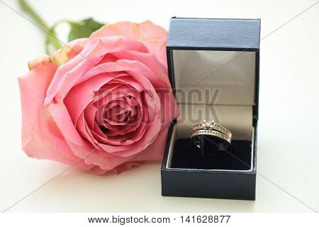 Engagement rings in box and pink rose