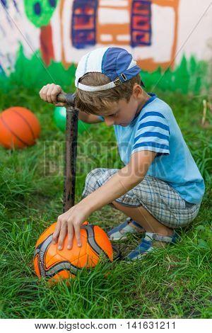 Boy Inflates Soccer Ball Pump
