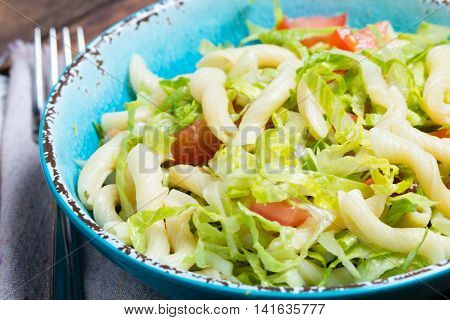Italian food. Mediterranian vegetables salad with pasta in blue bowl and napkin on wooden background. Copy space. Close up