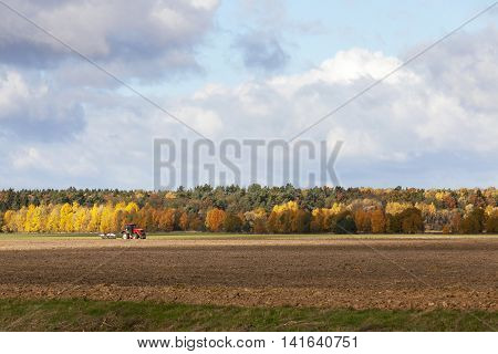 Agricultural field that plows the tractor in the background yellowed forest in autumn season