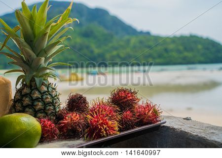 Plate full of tropical fruits over blurred seaview from restaurant