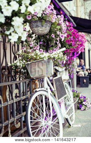 flower in basket of vintage bicycle on vintage wooden house wall, summer street cafe close up