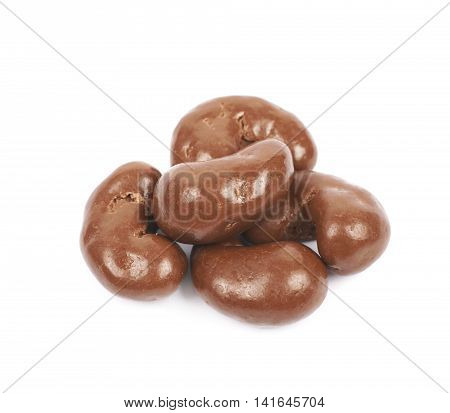 Pile of multiple chocolate coated cashew nuts isolated over the white background