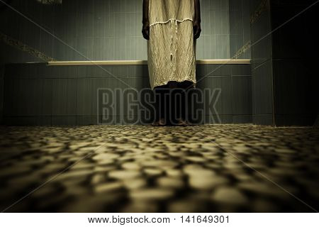 Scary person in white dress standing close to bathtub,Scary background for book cover