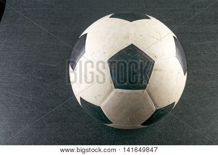 Dirty soccer ball on black background color