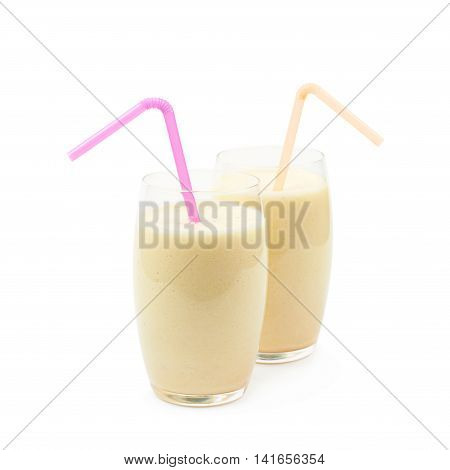 Two glasses of the milkshake cocktail served with a straw, composition isolated over the white background