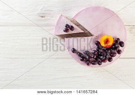 Cut piece fruit cheesecake decorated with grapes. Copyspace