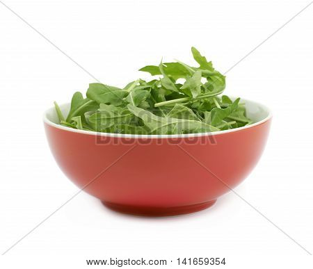 Red ceramic bowl full of rocket salad leaves isolated over the white background