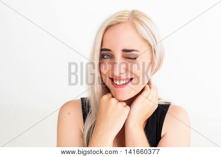 Young blonde-haired woman giving wink to camera. Close-up of attractive flirting winking blonde on white background, free space