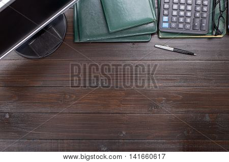 Office brown wooden desktop with monitor business card holder calculator glasses leather folder notebook and pen. Top view with copy space
