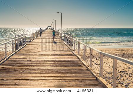Adelaide Australia - February 7 2016: Unrecognized barefoot woman walking along the Henley Beach Jetty on a warm sunny day.