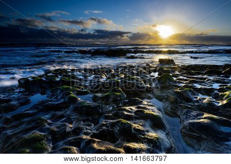 A New Day begins with a coastal sunrise as the low light picks out highlights on the limestone plateau and gentle waves lap against the shore