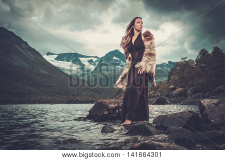 Nordic goddess in ritual garment near wild mountain lake in Innerdalen valley, Norway.