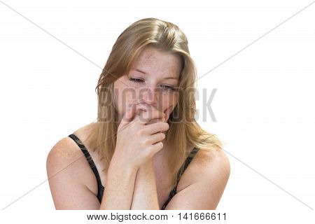 Bereaved redhead young woman with freckles is holding her face. All is isolated on the white background.