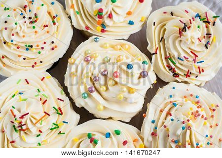Background Lot Of Cupcakes With Cream And Colored Sugar Sprinkles