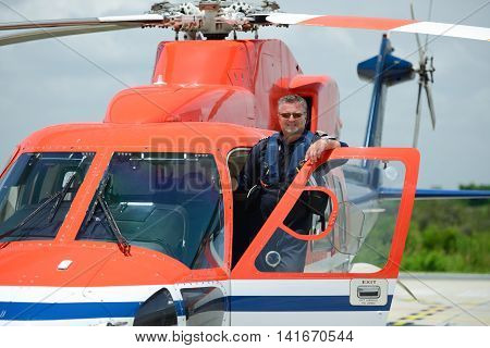 offshore helicopter pilot is standing on helicopter cockpit door