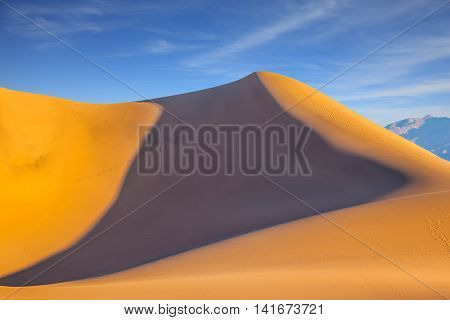Bright sunny morning in a Death Valley, USA. Mesquite Flat Sand Dunes. Bizarre twists of orange sand dunes