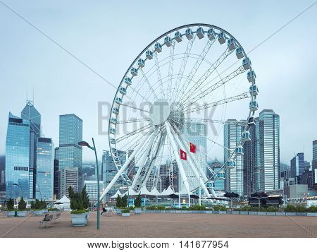Hong Kong island central quay with observation wheel on foreground. Modern city architecture