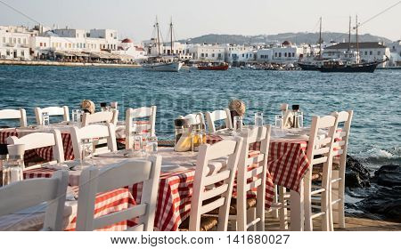 Empty chairs and dining tables in a traditional Greek at the beach restaurant at famous island of Mykonos in Greece