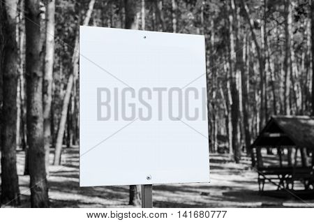 White billboard at the park with space for your advertisement. Black and whie tone