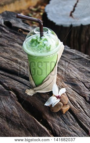 green tea frappe in wood table with nature background