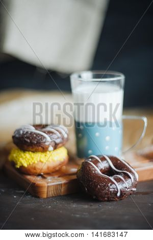 Colourfull donuts and glass of milk close up.