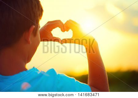 Happy little boy making heart with his hands over nature background. Joyful kid  showing heart from Hands with sunset inside. Vacation concept. Summer holidays. Tourism, vacation