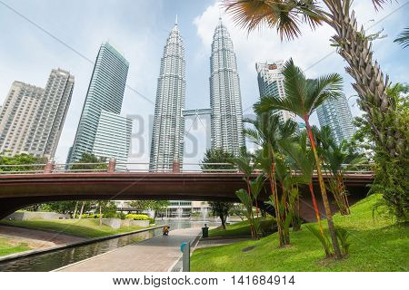 Kuala Lumpur Malaysia- October 9 2013: Petronas Twin Towers center in wide angle image in Kuala Lumpur flanked by architecturally modern high-rise office towers rise over footbridge and water feature