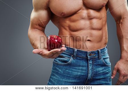 Strong Muscle Man holding a Red Apple in his hand over grey background. Shirtless athletic sexy male body builder holding an apple