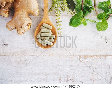 herbal pills on wooden spoon with ginger root and green plant on wood background.Above view