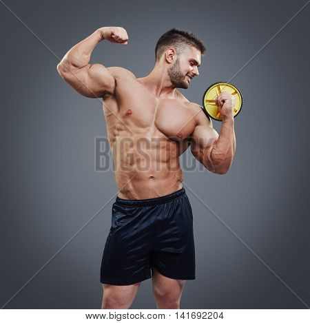 Portrait in studio of muscular male body isolated on grey background. Muscular athlete showing his bicep muscle and holding an ab wheel