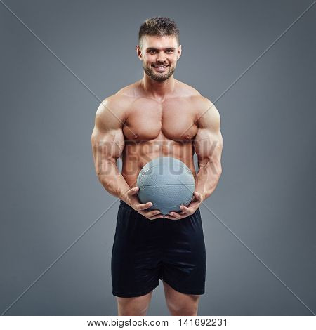 Smiling muscular man holding a medicine fitness ball on grey background. Strong bodybuilder presenting gym training accesories.