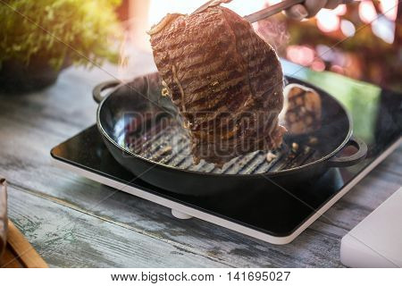 Piece of grilled meat. Tongs hold a steak. Beef cooked on frying pan. Food for lunch.