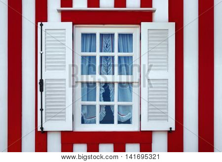 Single window on a red and white striped wall of a typical house in Costa-Nova, Aveiro, Portugal.