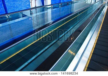 Escalator inside modern airport terminal, empty escalator