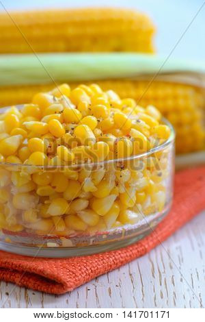Yellow steamed corn with salt and peper in a bowl