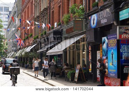 LONDON, UK - JULY 25: LONDON, UK - JULY 25 2016: A delivery cyclist passes several pedestrians on shop and restaurant lined Monmouth Street, in London's Covent Garden on July 25, 2016.