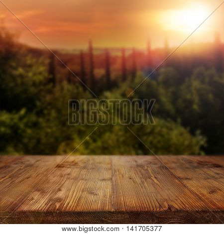 Rustic wooden table in Mediterranean Landscape with Setting Sun
